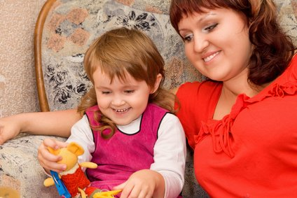 little girl and woman play a toy in a cosy room