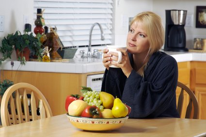 Contemplative Woman in Kitchen with Cup of Coffee.