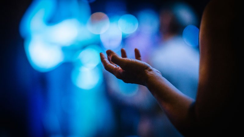 Woman from back with hands open to God during church service.