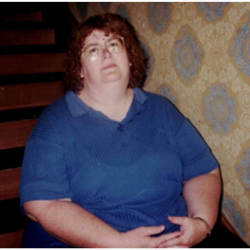Super morbidly obese woman tired sitting on stairs