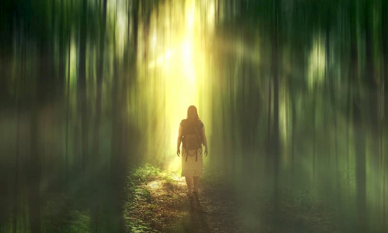 Woman with backpak on wallking into an ethereal area with green and yellow muted streaks of light